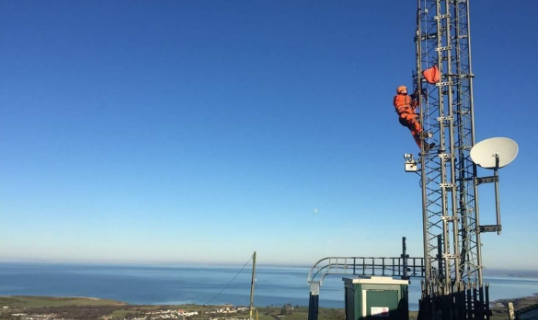 Telecommunications mast against sea background